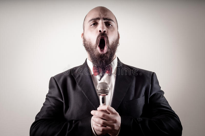 Funny elegant singer bearded. On vignetting background royalty free stock photography