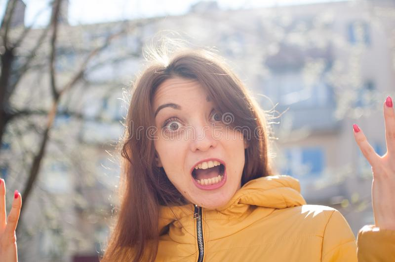 Funny emotional female portrait of young brunette in bright yellow jacket looking at the camera with unbelievable shock royalty free stock images