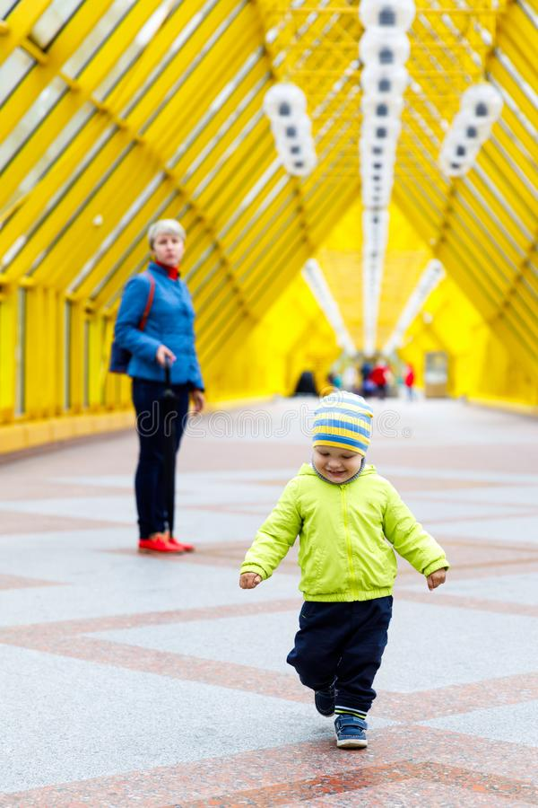 A funny emotional joyful boy walks by a model gait and dressed in an autumn jacket. adorable baby and his mom, family stock photo