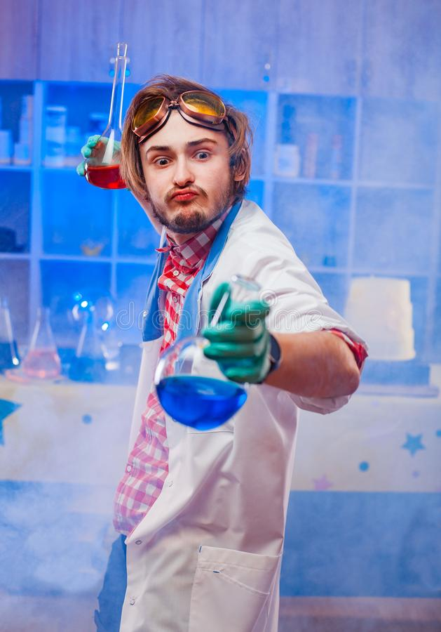 Funny professor holding flasks. Funny emotional young scientist holding flasks with colorful liquids in laboratory royalty free stock photos