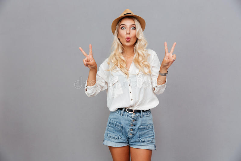 Funny excited young woman showing peace sign stock photo