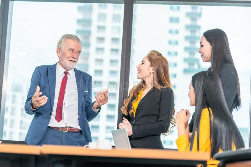 Executive boss is telling joke to team in office meeting for business success. Funny Executive boss is telling joke to team in office meeting for business royalty free stock photo