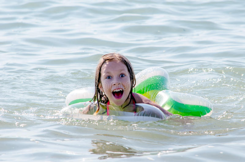 Funny expression on a swimming girl in lake Michigan stock photo