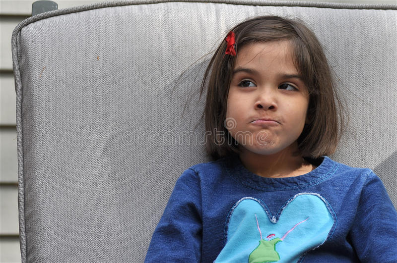 Funny Face. A cute little girl is asking for something she doesn't know. She shrugs with a funny expression on his face stock image