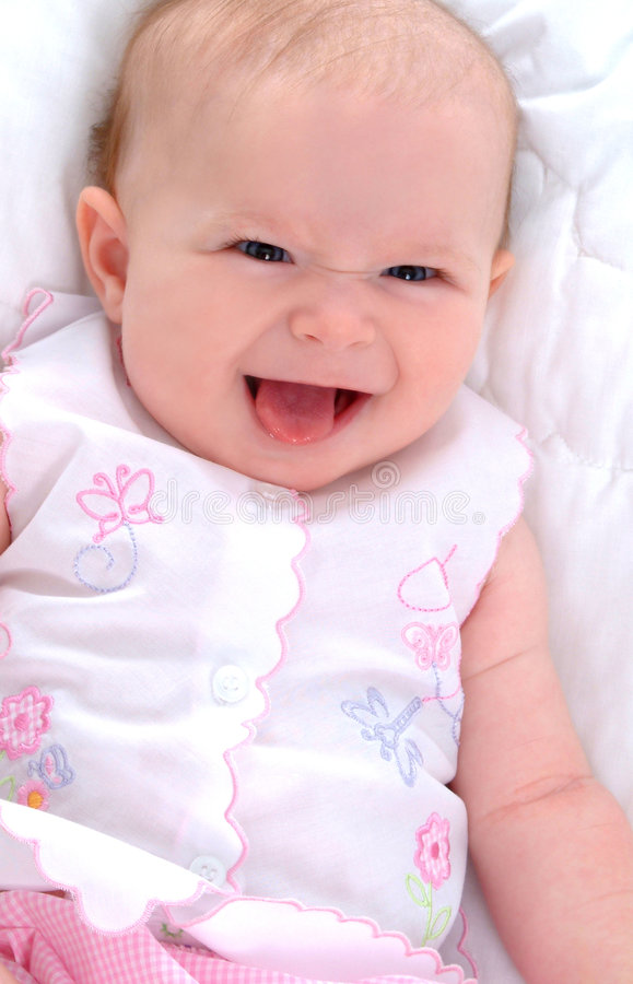 Funny Face. Baby girl lying on white blanket royalty free stock photos