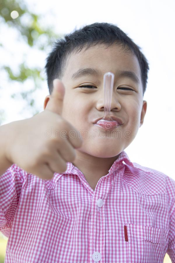 Funny face of asian children eating milk icecream in tea spoon in mouth stock image