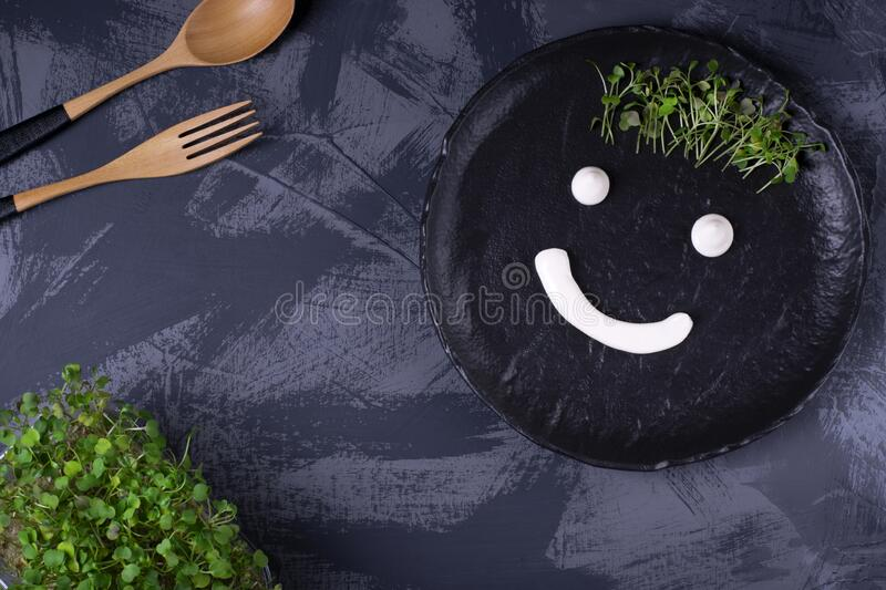 Funny face drawn with white sauce and microgreen on the black ceramic plate.