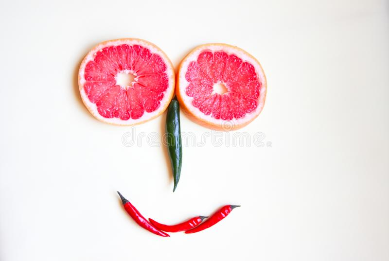 Funny face made of fruit and colored hot pepper. Funny face of red grapefruit and colored hot pepper royalty free stock images