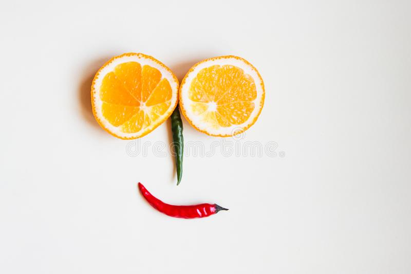 Funny face made of fruit and colored hot pepper. Funny face made of fruits, oranges and colored hot peppern royalty free stock photo