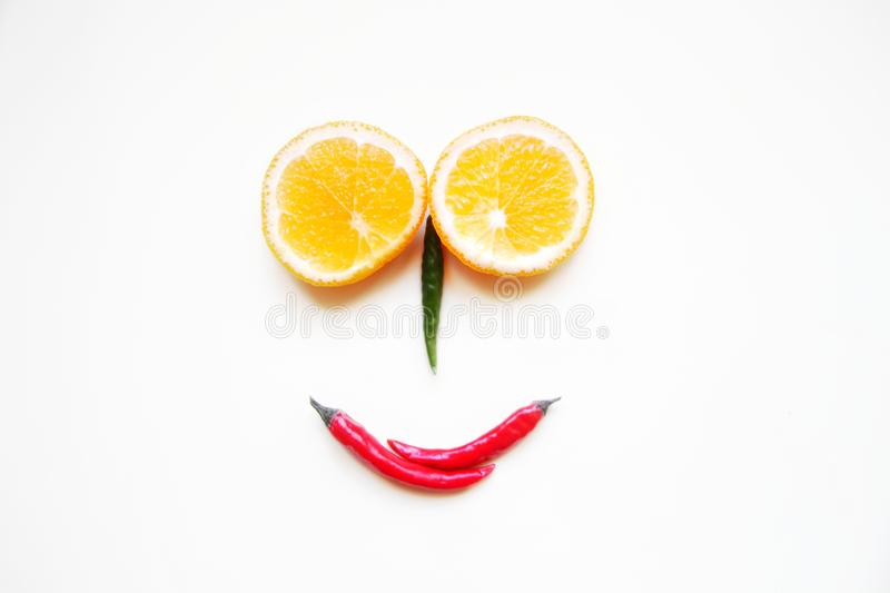 Funny face made of fruits and vegetables. two round oranges sliced, red and green peppers on a light background. Minimalism, close-up, selective focus, view stock image