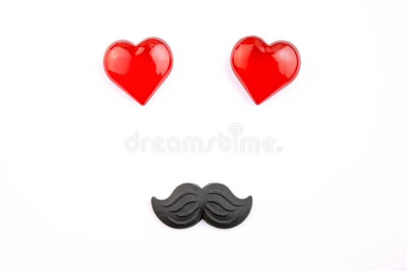 A funny face made of red hearts and plastic moustache on white background royalty free stock photos