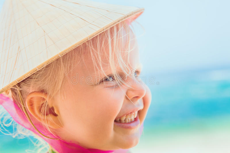 Funny face portrait of happy child in vietnamese straw hat royalty free stock photo