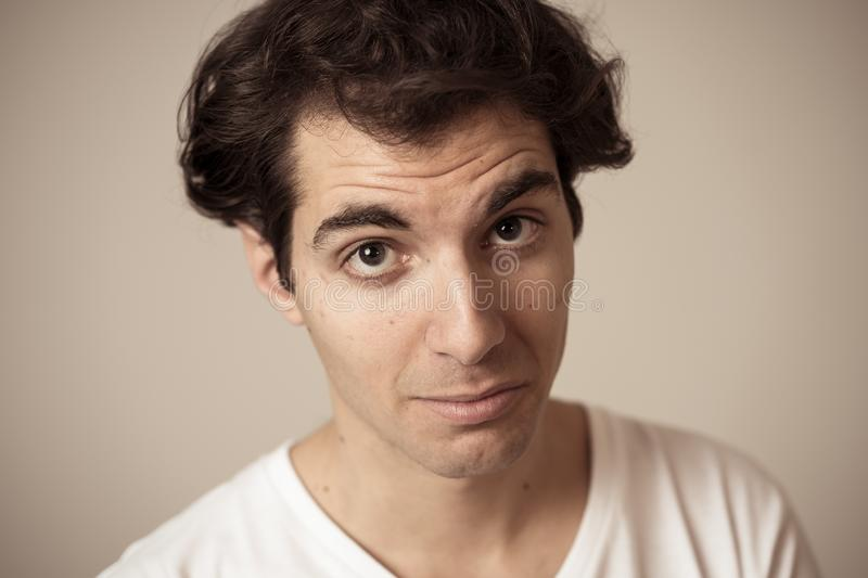 Funny face. Portrait of young man making amusing gestures. Portrait of young happy man with funny hilarious faces having fun. Millennial male making silly royalty free stock photo