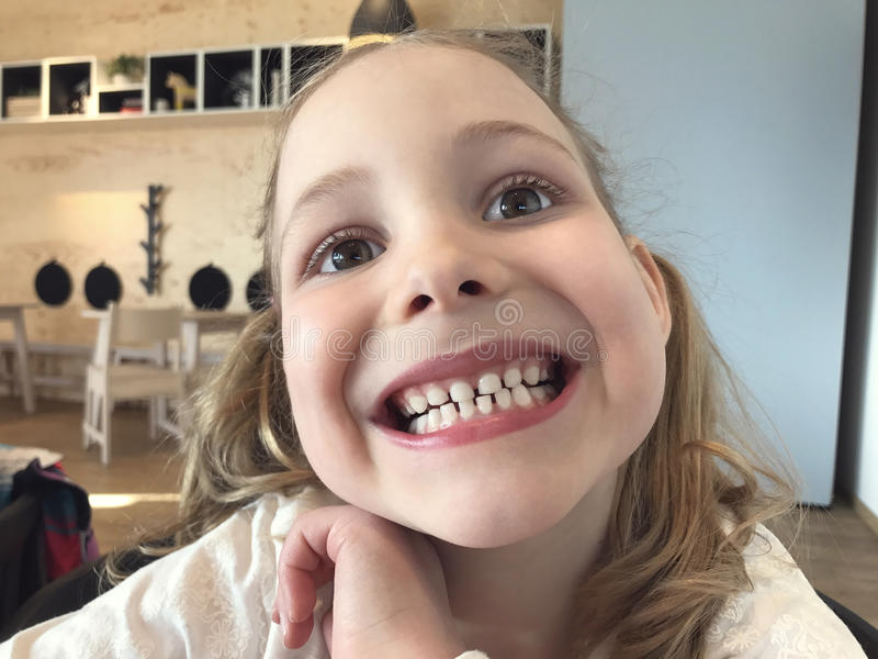 Funny face of small girl with white teeth royalty free stock photos