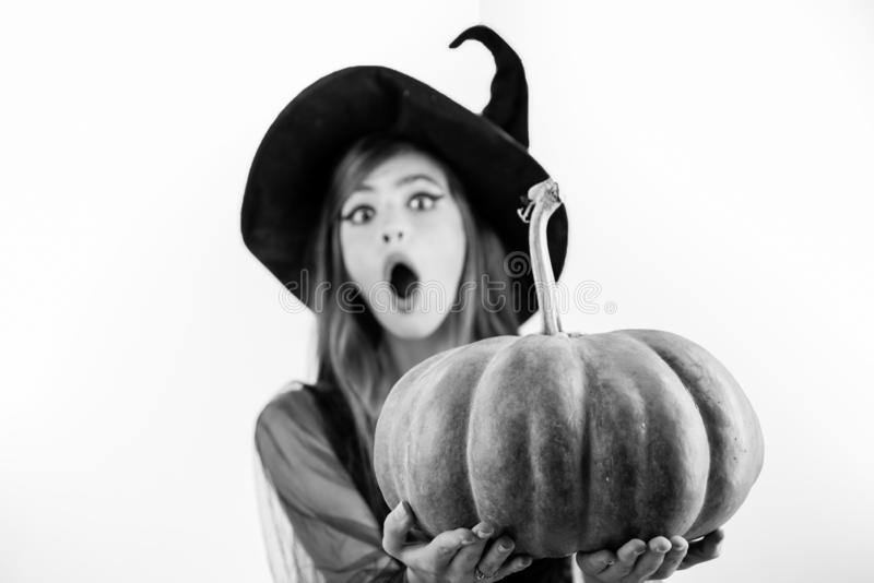 Funny face and Surprised woman. Woman posing with Pumpkin. Beautiful young surprised woman in witches hat and costume stock images