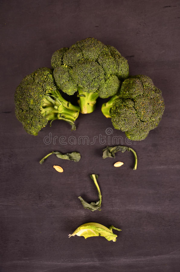 Funny face from vegetables on black ground stock photos