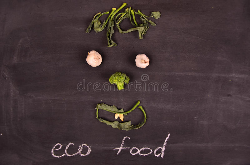 Funny face from vegetables on black ground stock photography