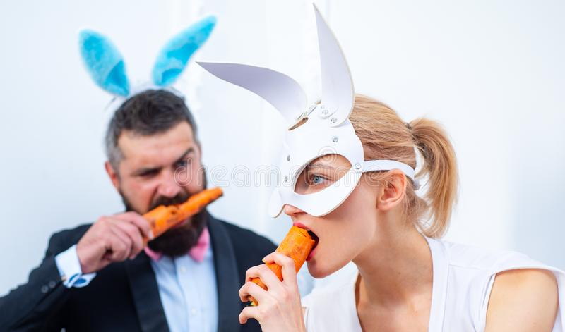 Funny Family celebrate Easter. Easter rabbits. Bunny couple. Happy holidays. Couple with bunny ears are eating carrot. royalty free stock photo
