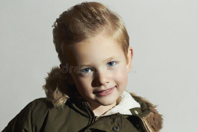 Funny Fashionable child in winter coat. fashion kids. children. khaki parka. smiling little boy. hairstyle. Portrait of funny Fashionable child in winter coat royalty free stock image