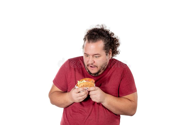 Funny fat man eating hamburger. Fast food, unhealty eat. Overweight and health problems royalty free stock photos