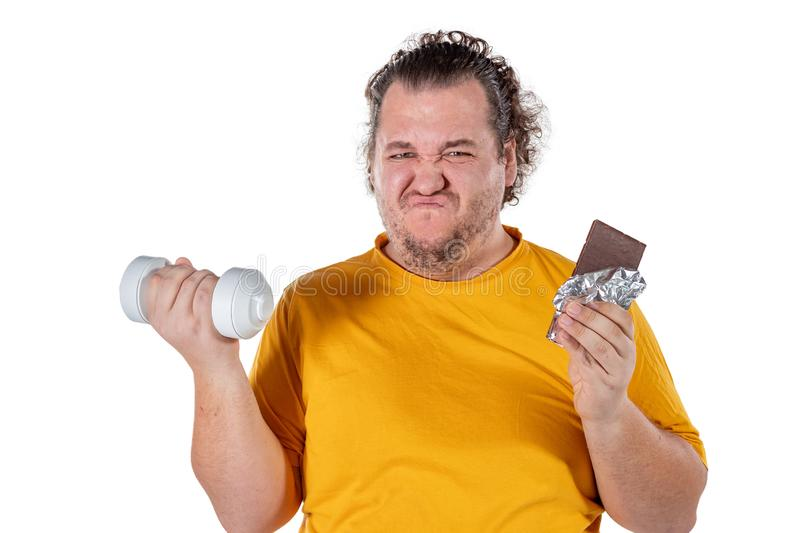 Funny fat man eating unhealthy food and trying to take exercise isolated on white background royalty free stock photos