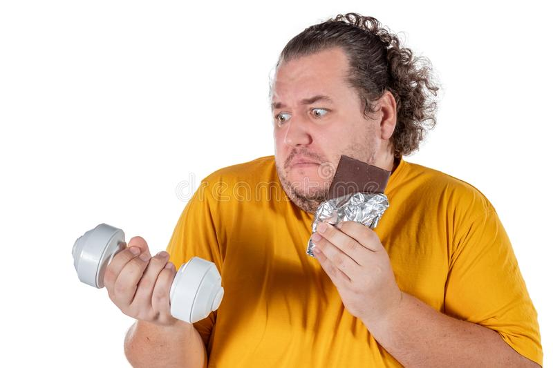Funny fat man eating unhealthy food and trying to take exercise isolated on white background stock photo