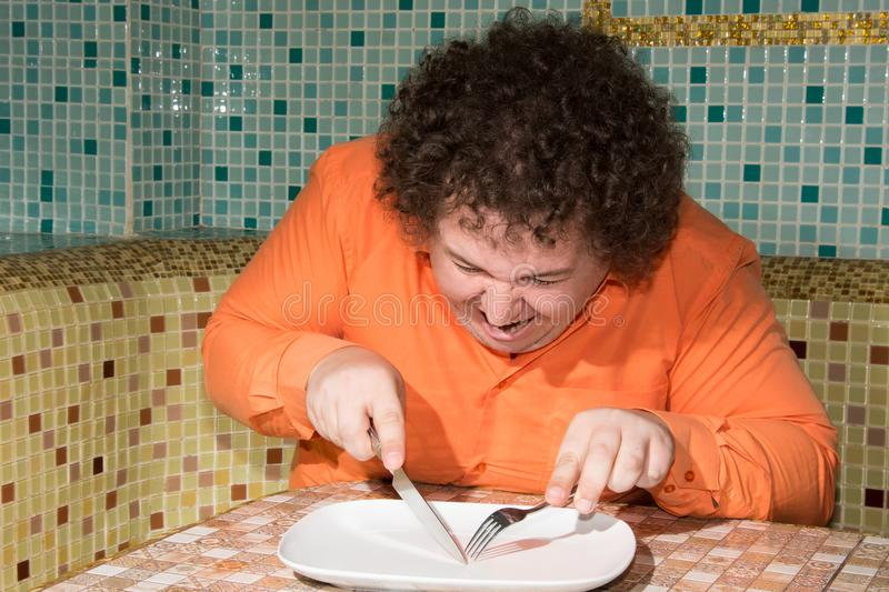 Funny fat man and an empty plate. Diet and a healthy lifestyle. royalty free stock photography