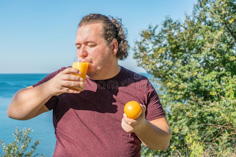 Funny fat man on the ocean drinking juice and eating fruits. Vacation, weight loss and healthy eating royalty free stock images