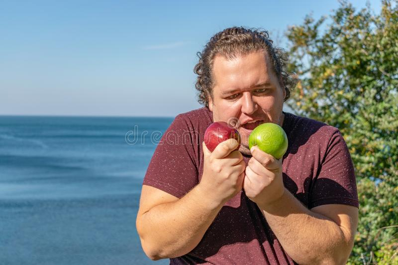 Funny fat man on the ocean eating fruits. Vacation, weight loss and healthy eating royalty free stock photos
