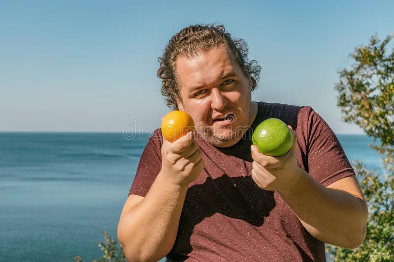 Funny fat man on the ocean eating fruits. Vacation, weight loss and healthy eating stock photo