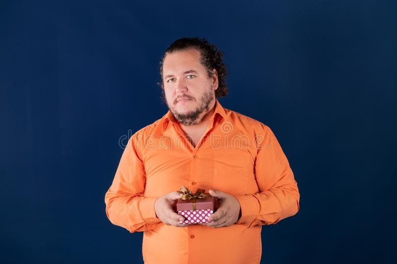 Funny fat man in orange shirt opens a box with a gift. Funny fat man opens a box with a gift. Birthday celebration stock photo