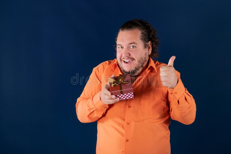 Funny fat man in orange shirt opens a box with a gift. Funny fat man opens a box with a gift. Birthday celebration royalty free stock photography