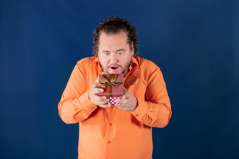 Funny fat man in orange shirt opens a box with a gift. Funny fat man opens a box with a gift. Birthday celebration royalty free stock photo