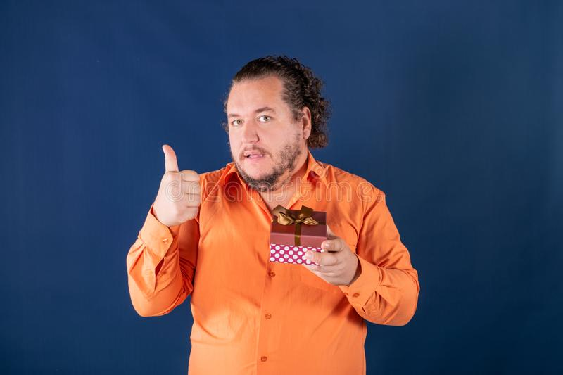 Funny fat man in orange shirt opens a box with a gift. Funny fat man opens a box with a gift. Birthday celebration royalty free stock images