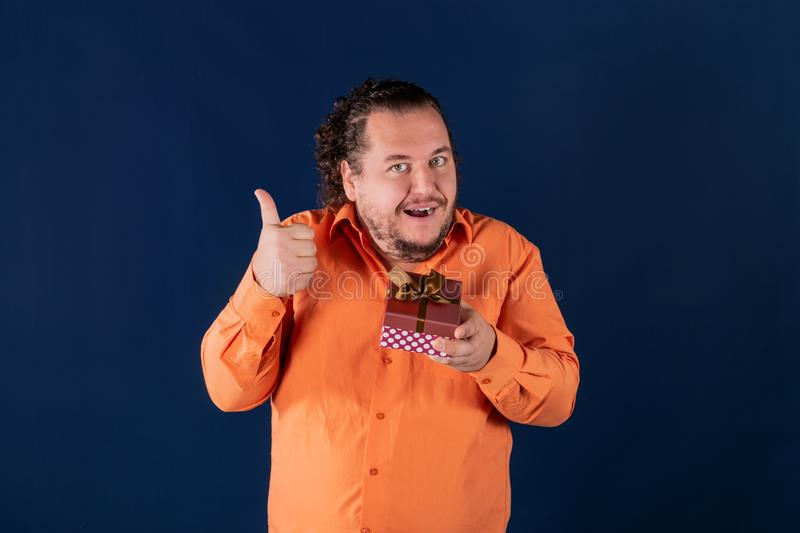 Funny fat man in orange shirt opens a box with a gift. Funny fat man opens a box with a gift. Birthday celebration stock images