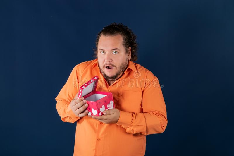 Funny fat man in orange shirt opens a box with a gift. Funny fat man opens a box with a gift. Birthday celebration stock image