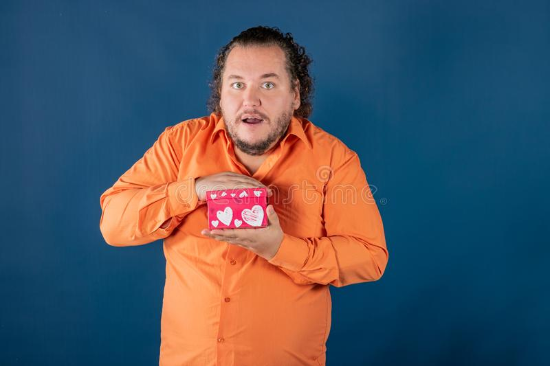 Funny fat man in orange shirt opens a box with a gift. Funny fat man opens a box with a gift. Birthday celebration royalty free stock photos