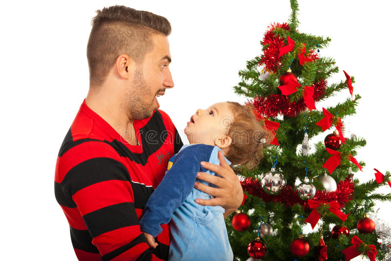 Funny father with baby. Boy in front of Christmas tree royalty free stock photo