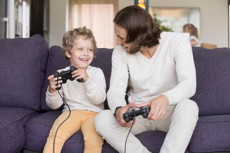 Father and son playing video games sitting on couch royalty free stock photo