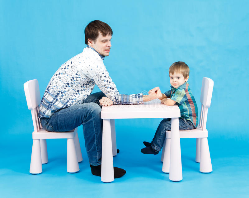 Funny father and little son competing in arm wrestling on blue. Background royalty free stock photos