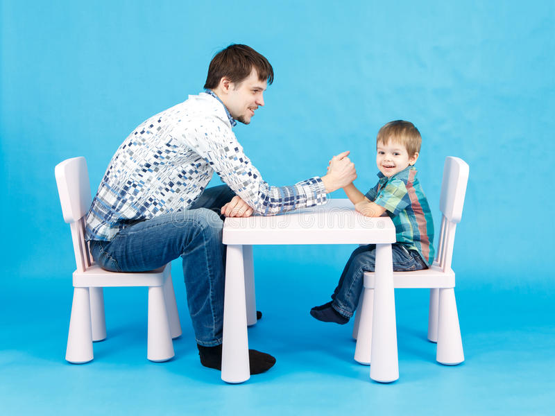 Funny father and little son competing in arm wrestling on blue. Background royalty free stock photography