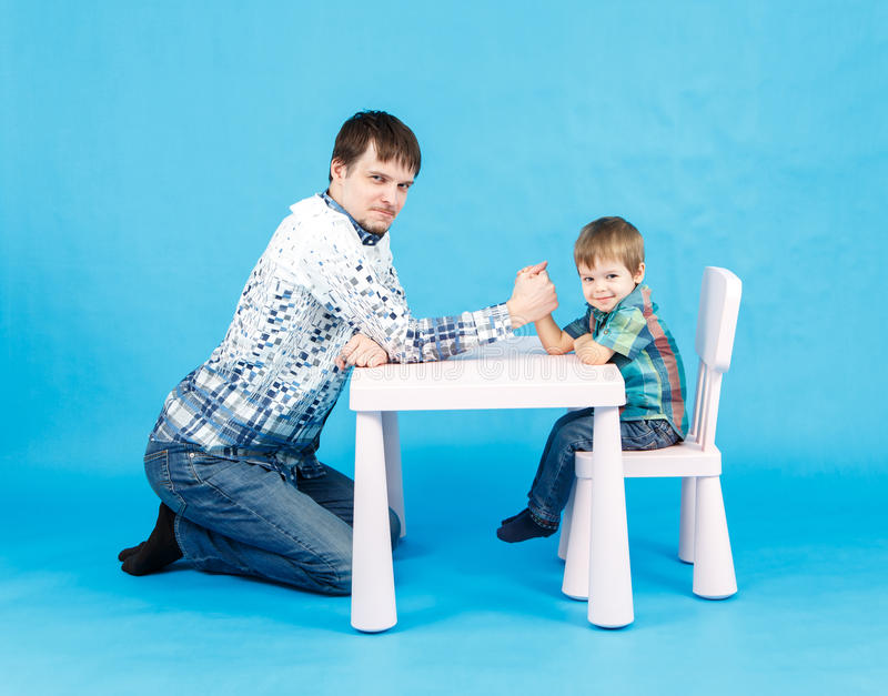 Funny father and little son competing in arm wrestling. On blue background royalty free stock image