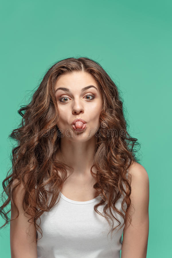 The funny Fdumbyoung woman`s portrait with happy emotions. The young Funny dumb woman`s portrait with happy emotions on studio background royalty free stock image