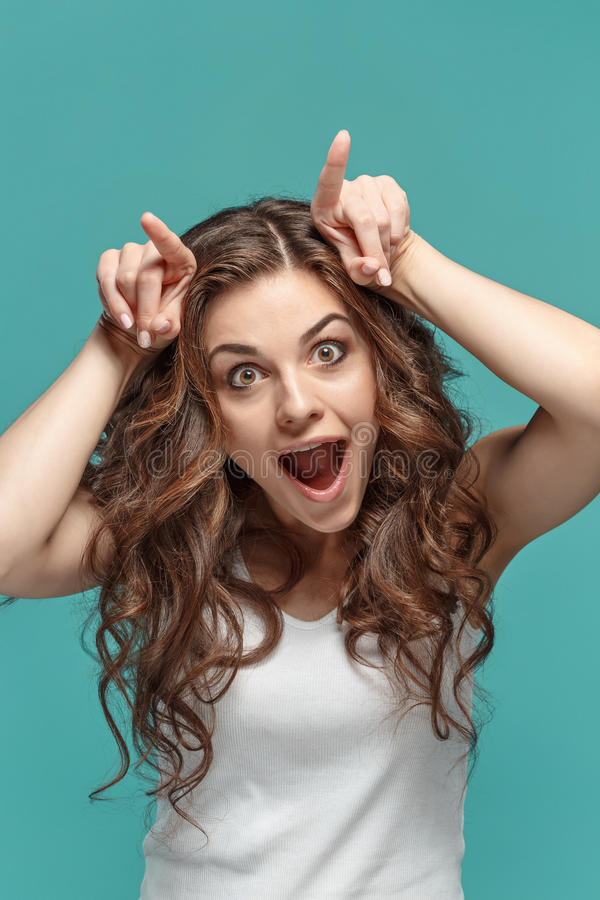 The funny Fdumbyoung woman`s portrait with happy emotions. The young Funny dumb woman`s portrait with happy emotions on studio background stock photos