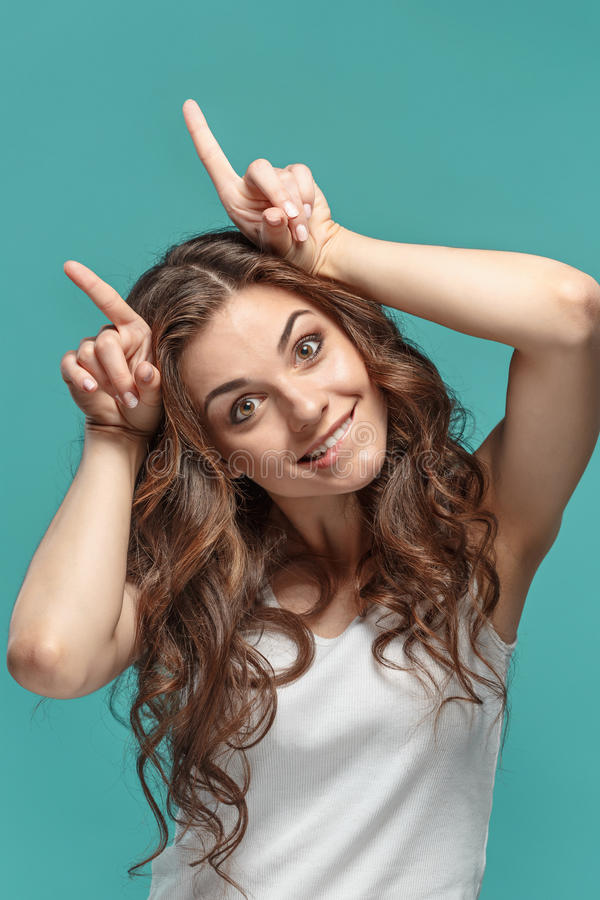 The funny Fdumbyoung woman`s portrait with happy emotions. The young Funny dumb woman`s portrait with happy emotions on studio background royalty free stock photography