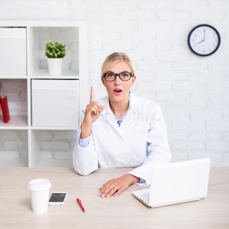 Funny female doctor or scientist showing idea sign in office royalty free stock photography