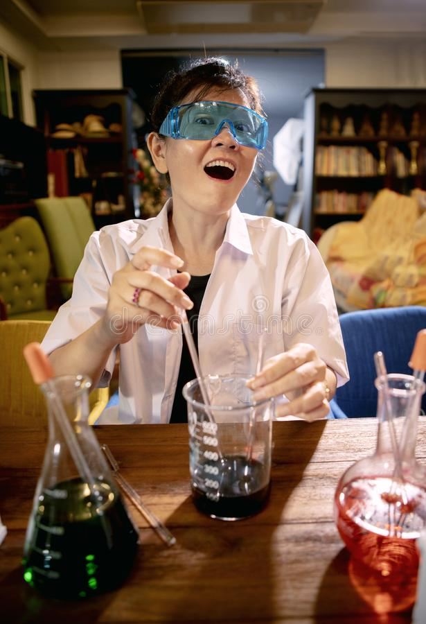 Funny female scientist in chemical laboratory royalty free stock photography