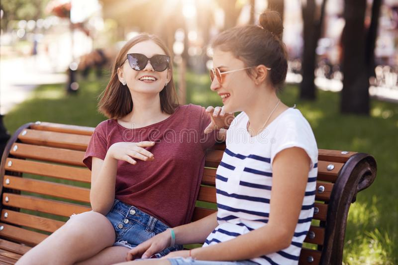 Funny female teenagers laugh joyfully while tell each other funny stories, dressed in casual clothes, sit on wooden bench, being i. N good mood, express positive stock image
