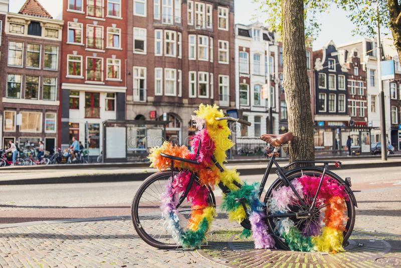 Funny festive bicycle on the street of Amsterdam, Netherlands. Vintage rusty bike with rainbow decoration. Popular travel destination in Europe. City life and stock image