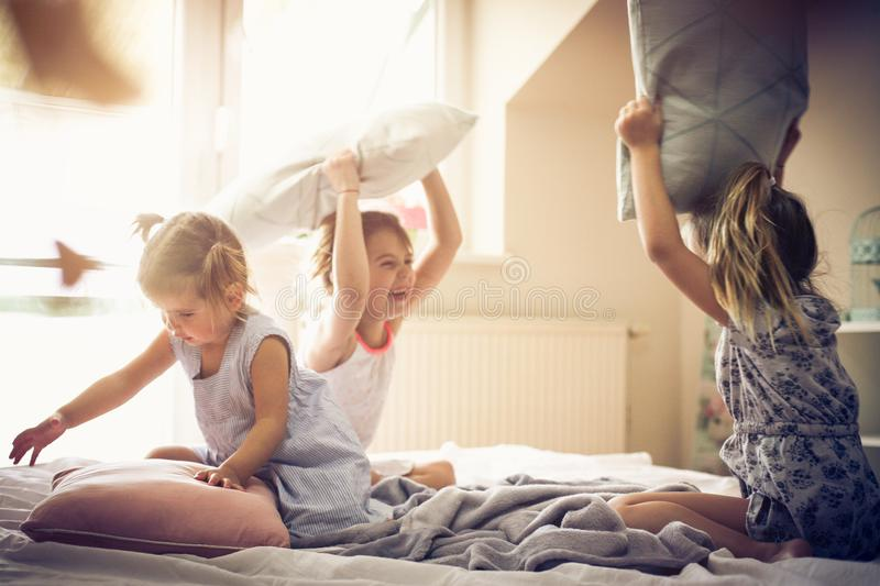 Funny fight. Three little girls playing in bed and having fight with pillow. Space for copy royalty free stock photos